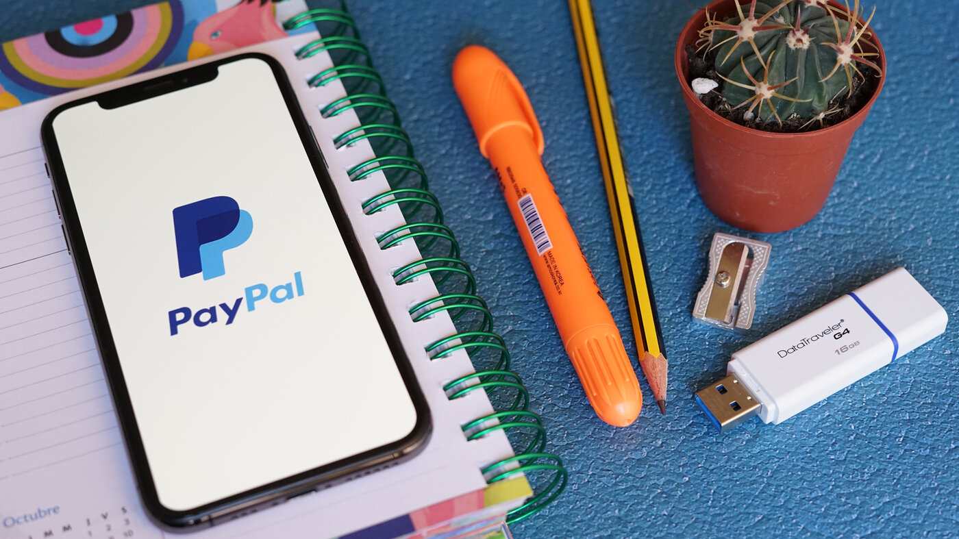 Paypal App on iPhone Screen on Opened Agenda Book with Stationery on a Blue Table