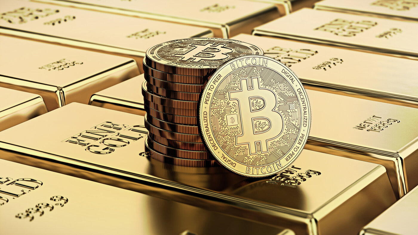 Bitcoin laying on stacked gold bars