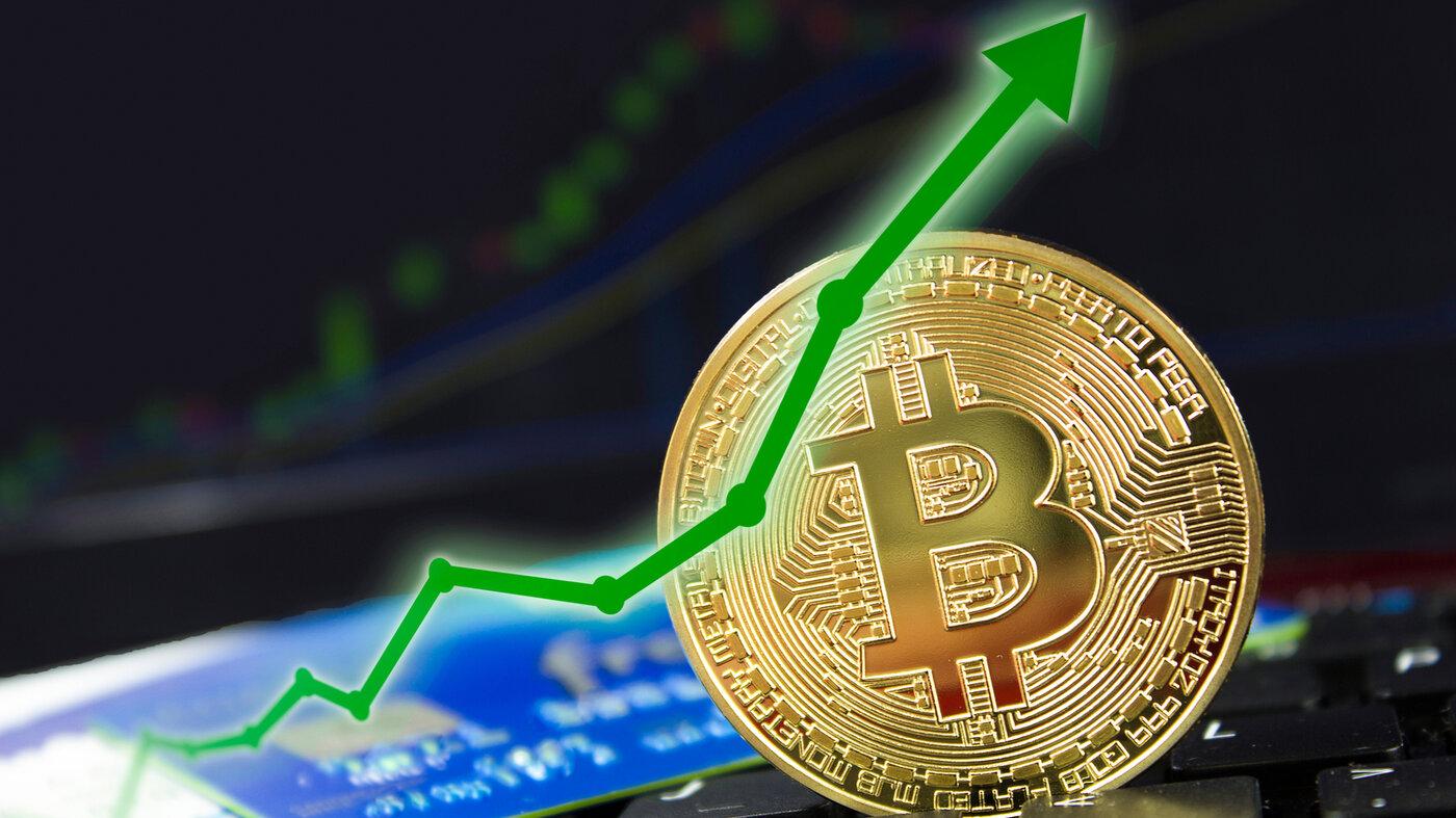 A gold Bitcoin next to a chart showing upwards market movement