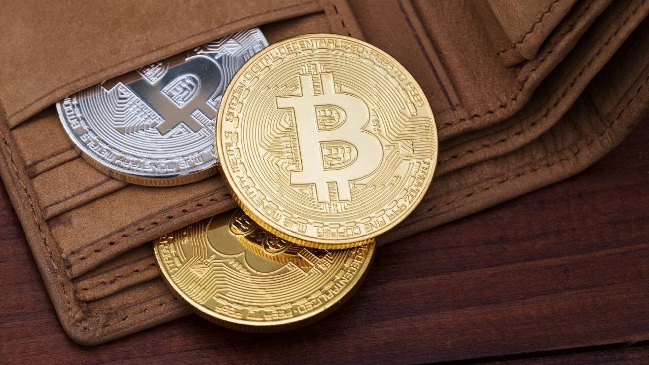 Gold and silver Bitcoins in a brown leather wallet