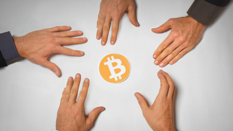 Hands reaching for Bitcoin