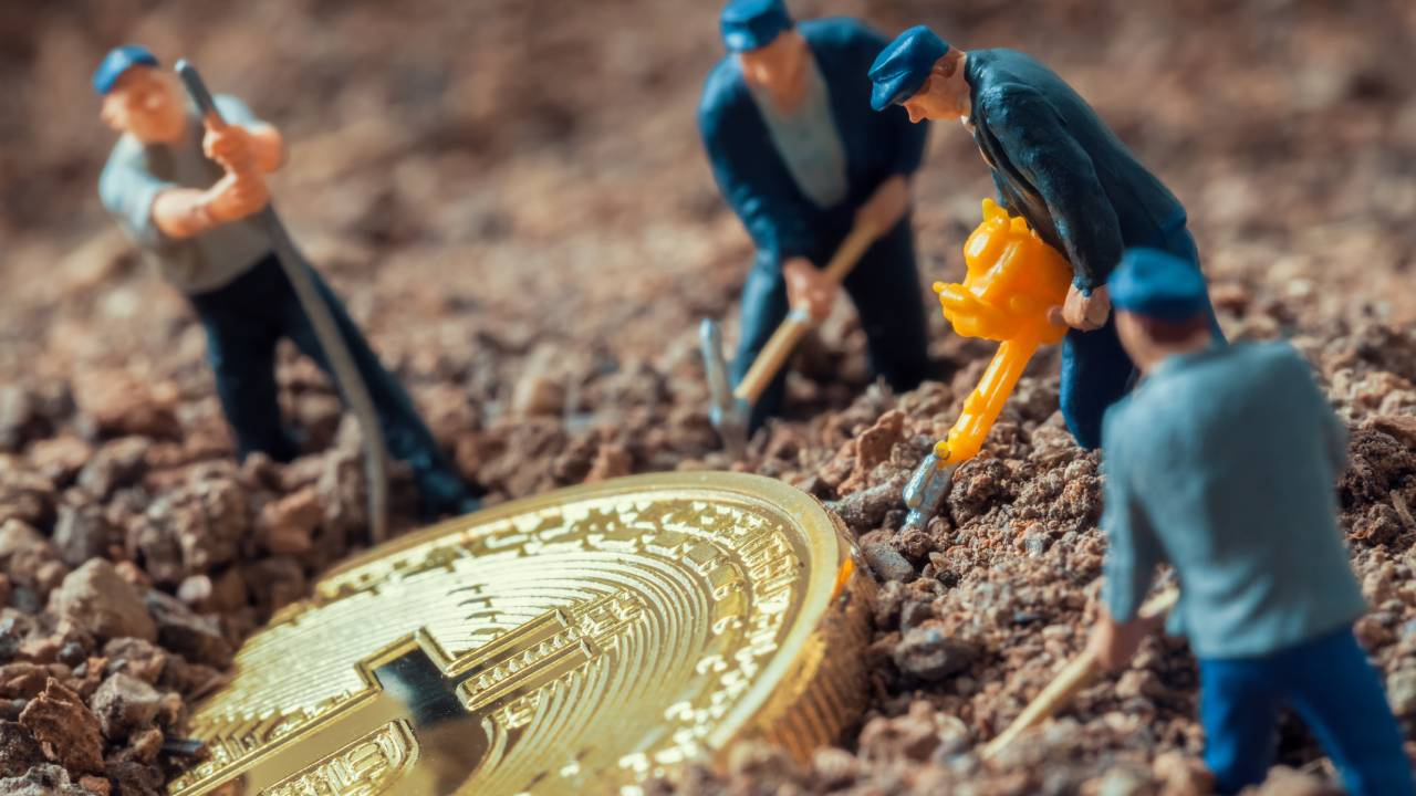 macro image of toy figures mining a gold Bitcoin