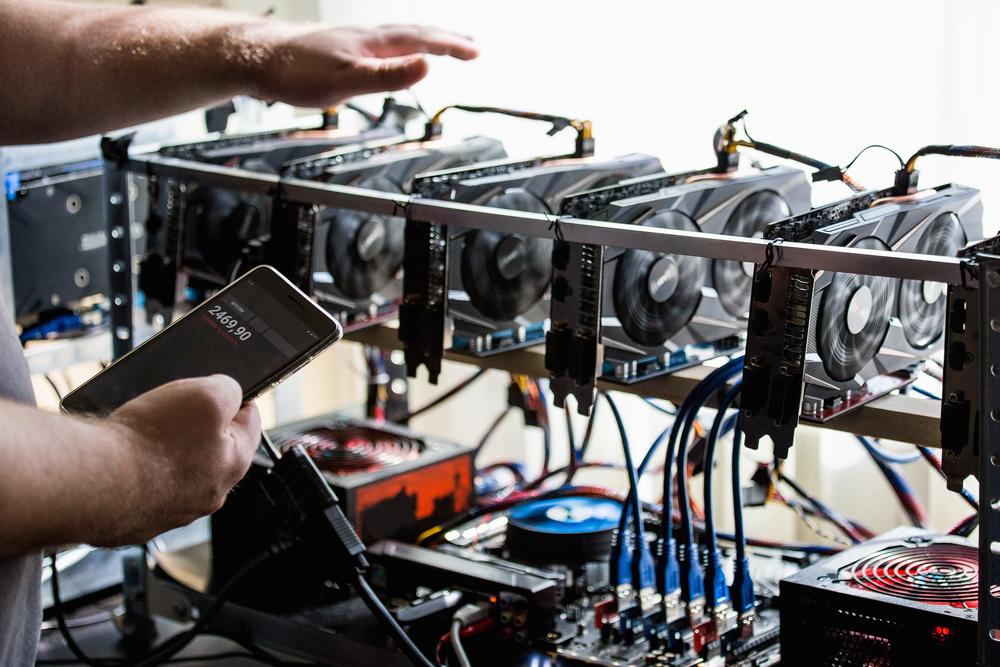person checking a bitcoin mining rig