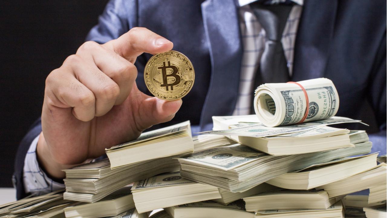 man holding a bitcoin atop a pile of US dollars