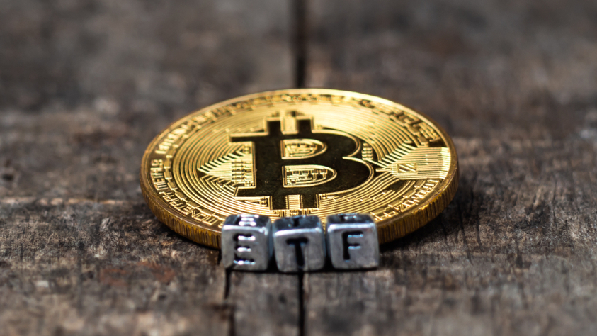 A Bitcoin coin next to ETF letters
